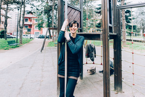 young handsome caucasian short brown hair woman having fun on a playground - childhood, freshness, carefree concept