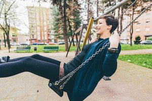 young handsome caucasian short brown hair woman having fun on a seesaw in a playground - childhood, freshness, carefree concept