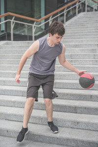 Young handsome caucasian sportive man bounching and playing basketball on a staircase in the city - sportive, fitness, healthy concept