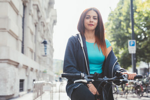 Young handsome caucasian sportive woman holding a bike outside in the city, looking at camera, smiling - transport, sportive, fitness concept