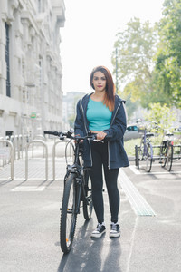 Young handsome caucasian sportive woman holding a bike outside in the city, overlooking at camera, smiling - transport, sportive, fitness concept