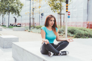 young handsome caucasian woman doing stretching outdoor in the city, doing yoga - training, sportive, healthy concept