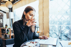 Young handsome caucasian woman sitting in a bar working with her laptop, drinking from a cup, looking the screen - business, technology, happiness concept
