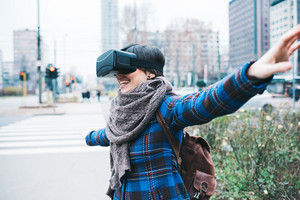 Young handsome caucasian woman using 3D viewer outdoor in the city smiling with arms wide open - happiness, futuristic, technology concept