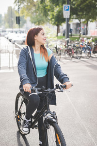 Young handsome cauciasian reddish hair woman riding a bike outside in the city, overlooking right, smiling - transport, sportive, fitness concept