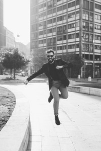 Young handsome contemporary business man jumping outdoor in city back light - success, positive, winner concept - black and white