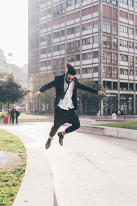 Young handsome contemporary business man jumping outdoor in city back light - success, positive, winner concept