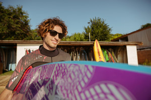 Young handsome curly man in sunglasses going to surf holding surfboard