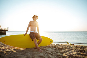 Young handsome curly resting while sitting on the surfboard at the beach