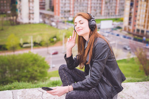 Young handsome eastern brunette girl listening music in a park in the city - technology, freedom, emancipation concept