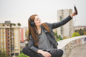 Young handsome eastern brunette girl listening music sitting on a small wall with city in background, taking a selfie with her smartphone - technology, music, vanity concept