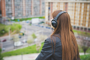 Young handsome eastern brunette girl listening music with headphones outdoor in the city view from behind - technology, freedom, emancipation concept