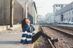 Young handsome eastern woman sitting on railway outdoor in the city having fun laughing - happiness, carefree, serene concept
