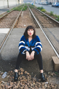 Young handsome eastern woman sitting on railway outdoor in the city looking at camera, serene - thoughtless, carefree, serene concept