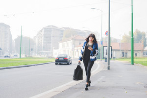 Young handsome eastern woman walking outdoor in the city, holding a smartphone and a bag, overlooking - technology, social network, business concept