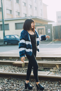 Young handsome eastern woman walking outdoor in the city, walking on rail, overlooking pensive - serious, thoughtful, pensive concept