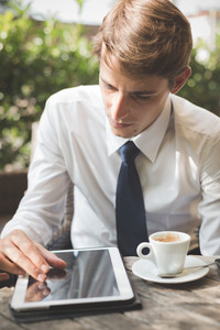 young handsome elegant blonde model businessman working with tablet and smart phone at the bar