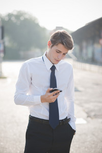 young handsome elegant blonde model man using smart phone in the city