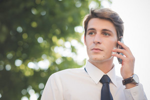 young handsome elegant blonde model man using smartphone in the city