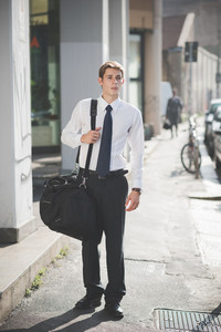 young handsome elegant blonde model man walking with sport bag in the city