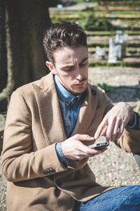 young handsome fashion model man calling with cellphone outdoors