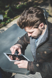 young handsome fashion model using tablet man outdoors