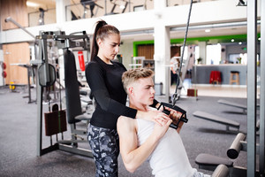 Young handsome fit man with his personal trainer working out on pull-down machine in gym. Bodybuilder exercising with cable weight machine.