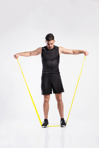 Young handsome fitness man in black sleeveless shirt working out with rubber band. Studio shot on gray background.