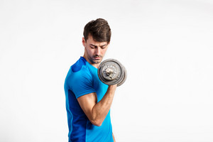 Young handsome fitness man in blue t-shirt working out with dumbbell. Studio shot on gray background.