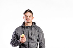 Young handsome fitness man in gray sweatshirt eating apple. Studio shot on white background.