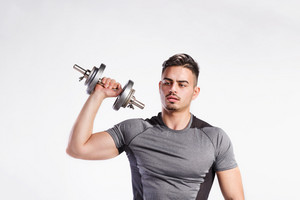 Young handsome fitness man in gray t-shirt working out with dumbbell. Studio shot on gray background.