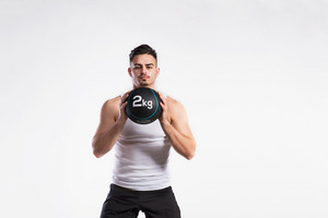 Young handsome fitness man in white sleeveless shirt holding medicine ball. Studio shot on gray background.