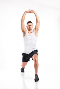 Young handsome fitness man in white sleeveless shirt stretching arms and legs. Studio shot on white background.