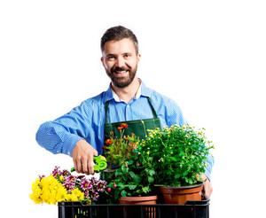 Young handsome gardener in green apron. Studio shot on white background