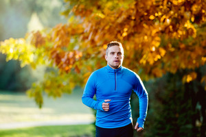 Young handsome hipster athlete in blue sweatshirt running outside in colorful sunny autumn nature