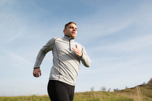 Young handsome hipster athlete in gray sweatshirt running in sunny autumn nature
