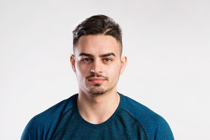 Young handsome hipster fitness man in blue t-shirt. Studio shot on gray background.