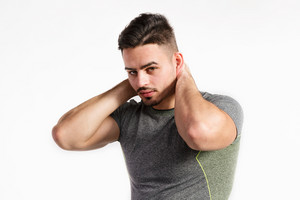 Young handsome hipster fitness man in gray t-shirt, holding neck. Studio shot on white background.