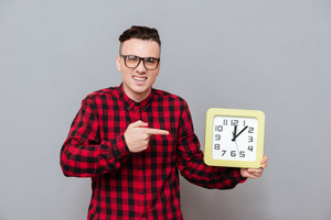 Young handsome Hipster in glasses holding a clock in one hand and pointing second hand on them. Isolated gray background