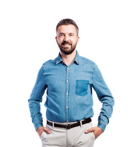 Young handsome hipster man in blue denim shirt, hands in pockets, studio shot on white background, isolated