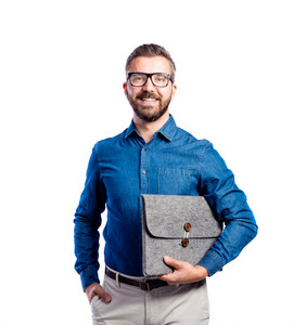 Young handsome hipster man in blue denim shirt, holding bag under his arm, hand in pocket, studio shot on white background, isolated