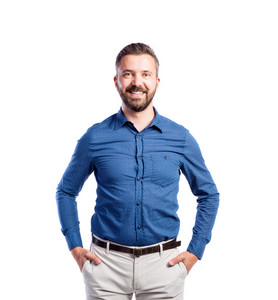 Young handsome hipster man in blue shirt, hands in pockets, studio shot on white background, isolated