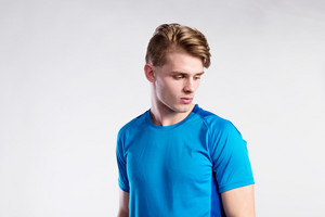 Young handsome hipster man in blue sports t-shirt. Studio shot on gray background.