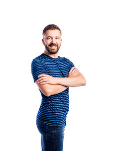 Young handsome hipster man in blue striped t-shirt, arms crossed. Studio shot on white background, isolated.
