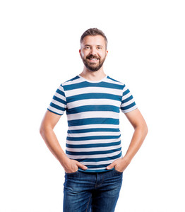Young handsome hipster man in blue striped t-shirt, hands in pockets. Studio shot on white background, isolated.