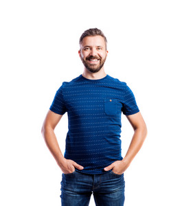Young handsome hipster man in blue t-shirt, hands in pockets, studio shot on white background, isolated