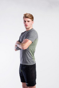 Young handsome hipster man in gray t-shirt, tattoo on his forearms, arms crossed. Studio shot on gray background.