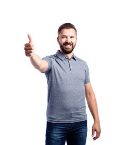 Young handsome hipster man in gray t-shirt, thumbs up. Studio shot on white background, isolated.