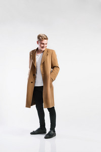Young handsome hipster man in long brown coat. Studio shot on gray background.