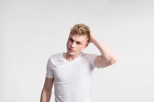 Young handsome hipster man in white t-shirt smiling. Studio shot on gray background.